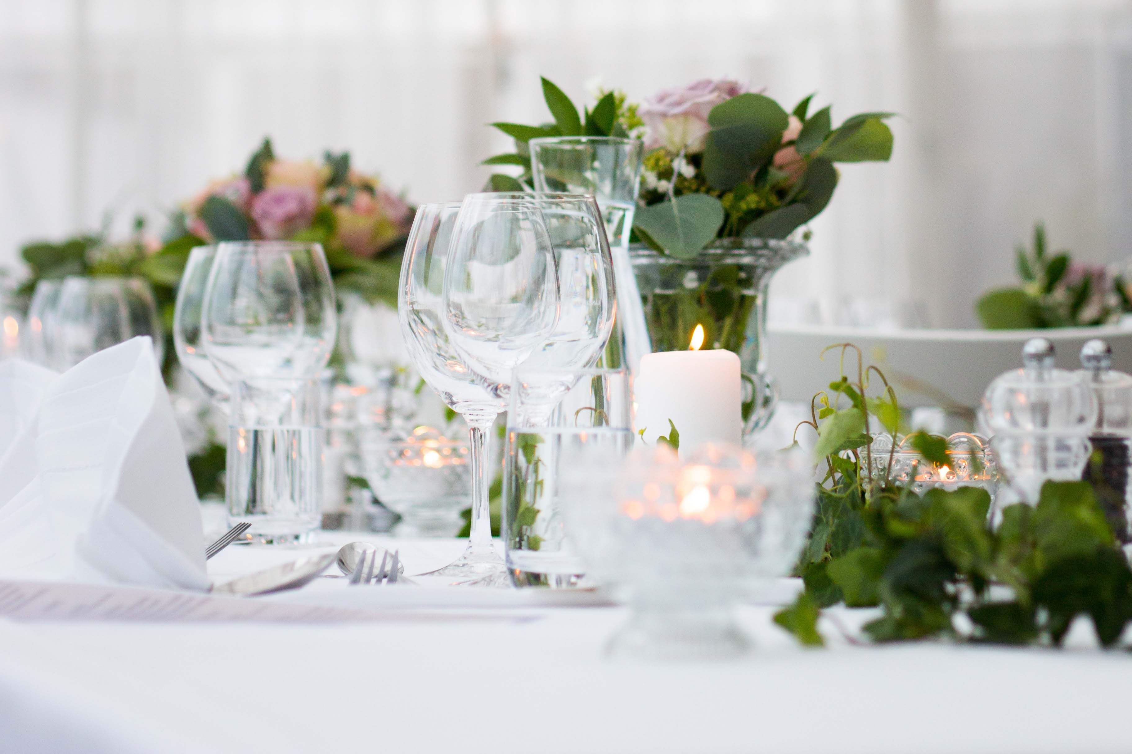 Empty wine glasses on white table with leaves, flowers and candles.